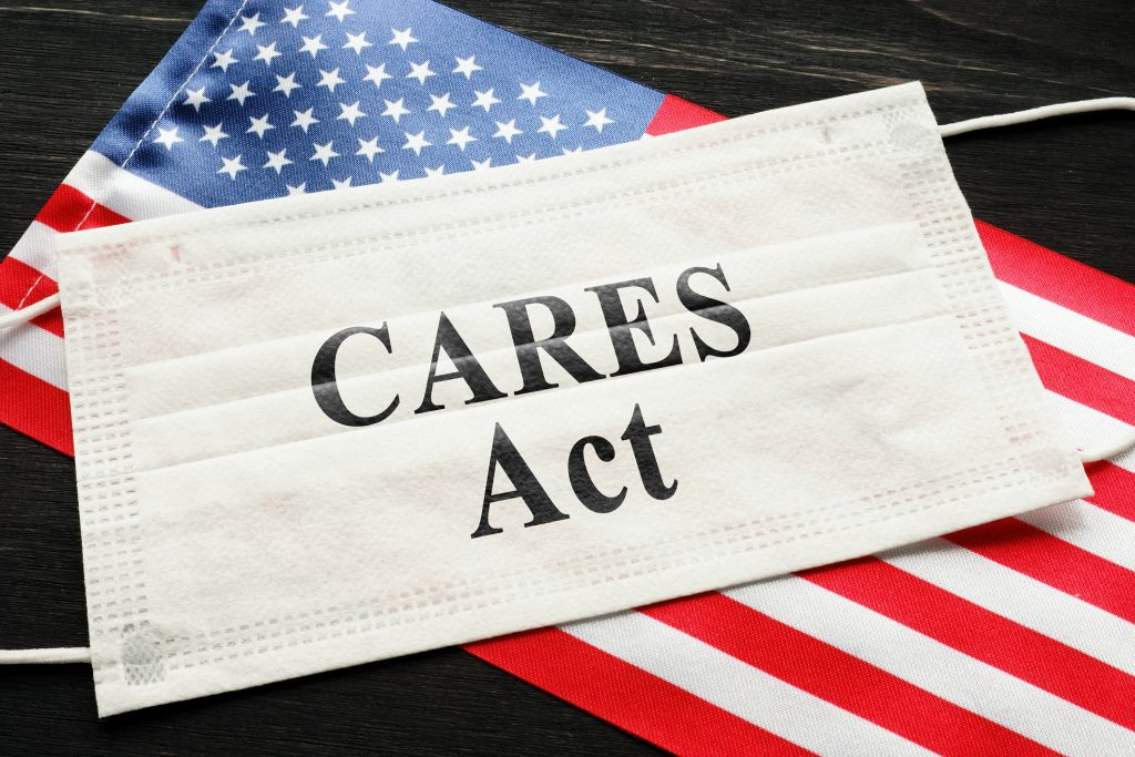 American flag and mask with sign cares act. Coronavirus Aid, Relief, and Economic Security law concept.